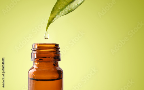 Photo Leaf and drop of natural medicine falling into jar isolated