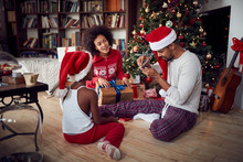 Happy African American Family With Girl And Christmas Gifts On Floor At Home
