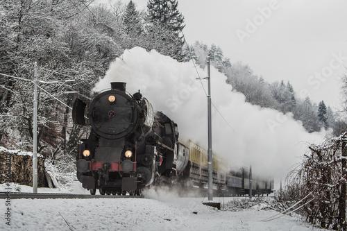 Fototapeta Christmas steam train on a gray winter day rushing towards camera and letting off steam obraz na płótnie