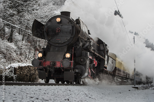 Obraz pociąg  swiateczny-pociag-parowy-w-szary-zimowy-dzien-pedzacy-w-kierunku-kamery-i-wypuszczajacy-pare