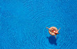 Aerial view of a woman in red bikini lying on a donut in the pool