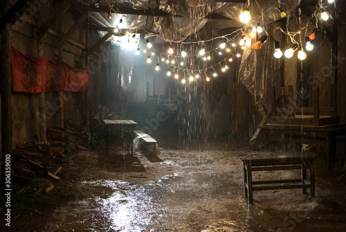 Fototapeta Silhouette of a man in a coat and hat in a dark alley on a rainy night obraz