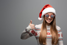 Beautiful Positive Woman In Christmas Sweater, Santa Hat And Sunglasses Showing Thumb Up, Isolated On Grey