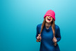 canvas print picture - funny laughing woman in knitted sweater with pink hat on eyes, isolated on blue