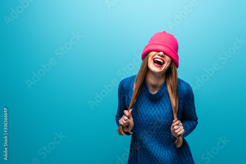 Cuadros en Lienzo funny laughing woman in knitted sweater with pink hat on eyes, isolated on blue