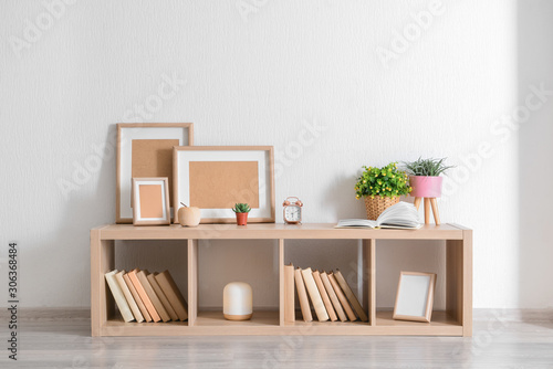 Fotomural  Stand with books and houseplants near white wall