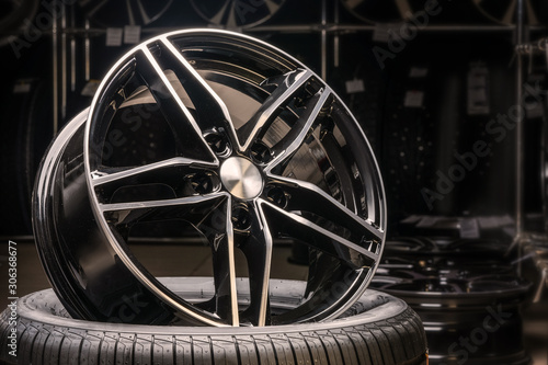 Foto new expensive cast aluminum disc wheel black color, photographed on the tire