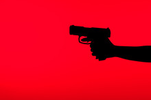 Cropped View Of Silhouette Of Criminal Woman Holding Gun In Hand Isolated On Red