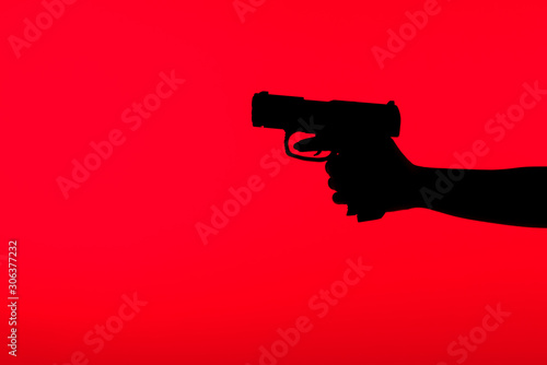 Fotografia cropped view of silhouette of criminal woman holding gun in hand isolated on red