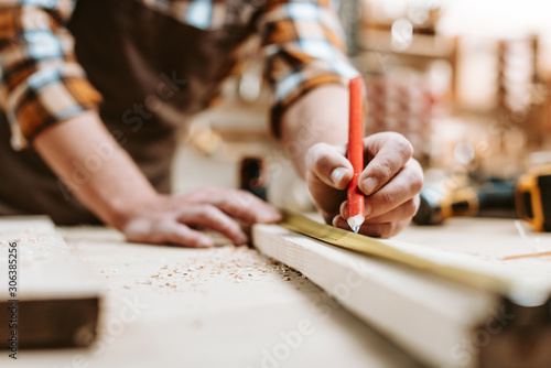 Photo cropped view of man holding pencil near wooden plank and measuring tape