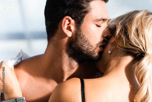 Obraz na plátně Shirtless businessman kissing blonde colleague