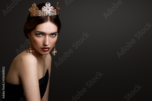 Fototapeta Close-up portrait beautiful girl with red lipstick in golden crown and earrings