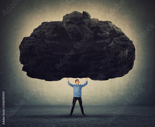 Fotomural Brave man making effort facing life problems as holding a huge boulder about to squeeze him