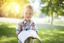 Closeup Shot Of A Child Holding An Open Bible While Looking At The Camera With Blurred Background