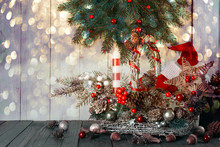 Christmas Background With Wicker Basket, Santa Boot And Hat, Candle And Star, Fir Tree, Acorns, Pine, Spruce Cones On Table, New Year Winter Holiday Home Natural Material Decor, Glowing Festive Bokeh.
