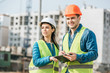 Female surveyor talking to smiling colleague with clipboard