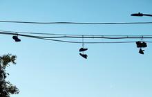 Silueta De Zapatillas Colgadas De Un Cable Ante Un Cielo Azul Despejado En Nueva York