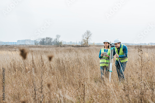 Fototapeta Surveyors with digital level and tablet working in field
