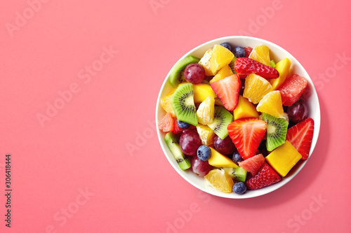 Fresh fruit salad on pink background - 306418444