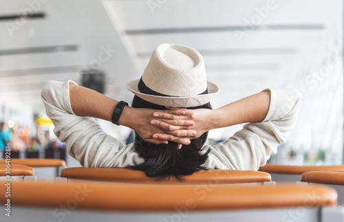 Asian traveler is relaxing while waiting for the flight at the airport. Holiday, travel, summer and Vacation. Rear view. Holding head with hands.