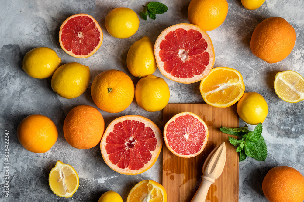 Top view on fresh citrus fruits composition with oranges, lemons, grapefruits and mint, grey background with wooden cutting board and squeezer or hand press <span>plik: #306422247 | autor: Alexander</span>