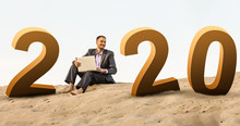Businessman Sitting Alone In The Empty Desert Happy New Year 2020 Numbers At Sunrise