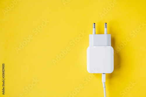 Foto Mobile charger and USB Cable on yellow background