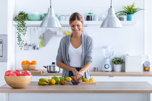 Pretty Young Woman Preparing Fruit Drink In The Kitchen At Home.