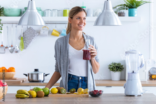 Pretty young woman looking to sideways while drinking fruit juice in the kitchen at home Fototapeta