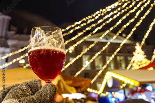 CLOSE UP Person wearing woollen gloves holds up a glass of delicious mulled wine Canvas Print