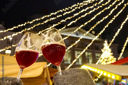 CLOSE UP: Two tourists wearing grey gloves toast with glasses of red mulled wine Canvas Print