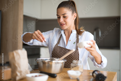 Photographie Young woman in kitchen preparing lunch