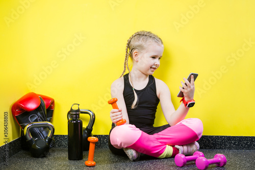 Valokuvatapetti Young child girl with a mobile phone sitting on the floor near the dumbbells, boxing gloves and a bottle of water on the floor