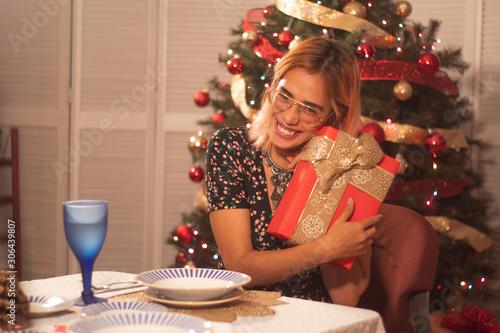 joven mexicana disfrutando de regalos en frente de árbol de navidad fiestas Canvas Print