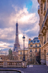Paris, France - November 24, 2019: Small paris street with view on the famous paris eiffel tower on a cloudy day with some sunshine