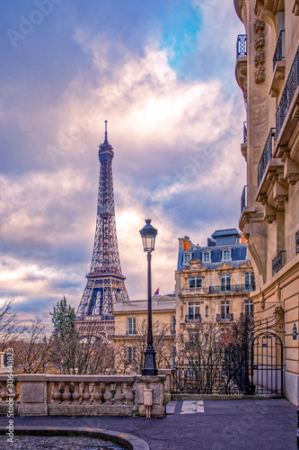 Paris, France - November 24, 2019: Small paris street with view on the famous paris eiffel tower on a cloudy day with some sunshine - 306440823