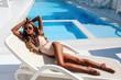 Leinwanddruck Bild - beautiful sensual woman with blond hair in elegant swimming suit relaxing in luxurious white villa