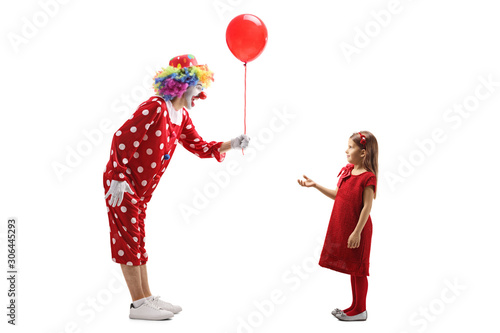 Photo  Clown giving a red balloon to a little girl