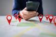 Leinwandbild Motiv Map With Red Location Marker And Mobile Phone