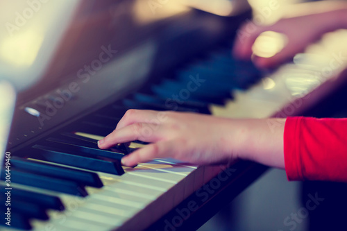 Closeup kid's hand playing piano on stage with lighting. Favorite classical music. There are musical instrument for concert or learning music. The concept of musical instrument. - 306449460