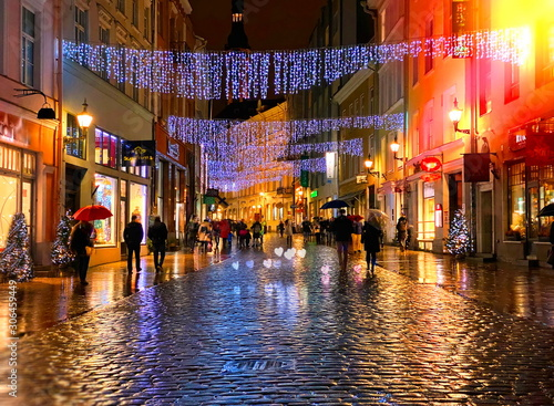 fototapeta na lodówkę Rainy Autumn Travel to Europe in the City Christmas Tallinn Old town street night light people walking with umbrellas rain drops reflection on wet asphalt soft blurred light lifestyle Tilt Shift