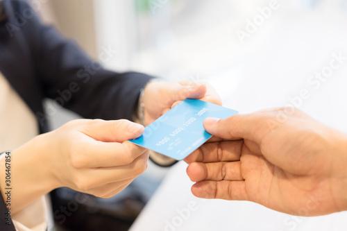 Fotografía クレジットカードを店員に手渡す女性・パーツカット(決済・支払い・キャッシュレス)