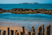 Wooden Wave Breakers In Saint Malo In Brittany, France Overlooking The Beach, Natural Pool And Fort Islands On A Sunny Day With Green Waters And Golden Sand.