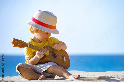 Obraz Kid plays on ukulele or small guitar at sea beach - fototapety do salonu