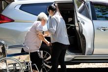 Asian Female Caregiver Helping...