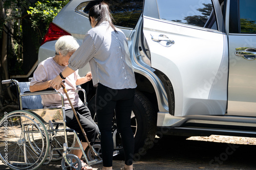 Obraz Asian female caregiver helping disabled elderly woman in wheelchair to get into the car,helpful daughter care and support senior mother to stand up from wheelchair in outdoor, caring for old people - fototapety do salonu