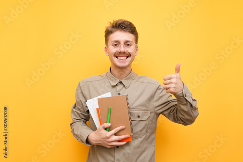 Portrait of a cheerful nerd in a shirt and glasses stands on a yellow background with books and exercise books in his hands, looks in camera, shows his thumb up and smiles Canvas Print