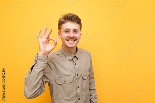 Cuadros en Lienzo Happy guy with mustache and glasses shows OK gesture and smiles against yellow background, looks into camera and wears shirt