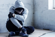 Unhappy Guy In Hood Is Sitting On Cardboard On Floor In Abandoned Building. Homeless Sad Man Lost Everything Because Of Addiction. Social Problems In Society. Loneliness And Depression Concept.