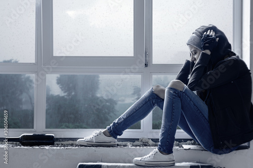 Fotomural Lonely, depressed, upset young woman in hood is sitting on windowsill and crying in abandoned building